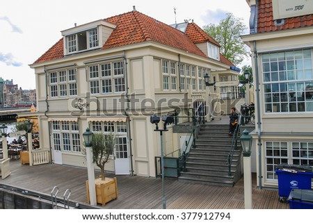 Amsterdam, Netherlands - June 20, 2015: People near cafe on the waterfront of canal in Amsterdam