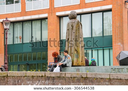 Amsterdam, Netherlands - June 20, 2015: People sit near the statue of Spinoza on the waterfront of canal in Amsterdam - stock photo