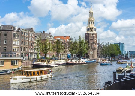 AMSTERDAM, NETHERLANDS - JUNE 16, 2013: The Montelbaanstoren tower on Oudeschans canal in Amsterdam, Netherlands, built in 1516 for the purpose of defending the city. - stock photo