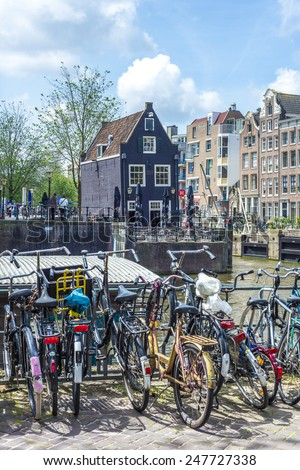 AMSTERDAM, NETHERLANDS - JUNE 15, 2013: Typical bicycles, the most popular transportation system in Netherlands, parked on Amsterdam bank canal - stock photo