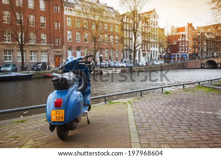 AMSTERDAM, NETHERLANDS - MARCH 19, 2014: blue Vespa scooter stands parked on the canal coast embankment - stock photo