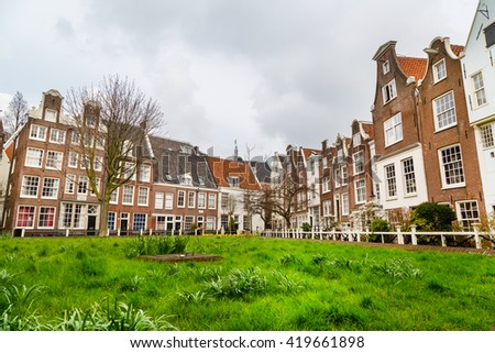 Amsterdam, Netherlands - March 31, 2016: Colorful view of Begijnhof courtyard with historic Holland houses in Amsterdam, Netherlands - stock photo