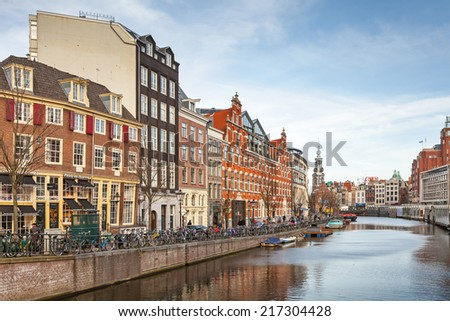 AMSTERDAM, NETHERLANDS - MARCH 19, 2014: Living houses along the canal embankment in spring day. Ordinary people walk on the coast - stock photo