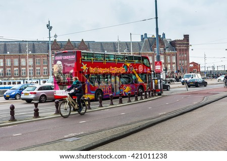 Amsterdam, Netherlands - March 31, 2016: Red hop on hop off sightseeing tour bus and historic houses in Amsterdam, Netherlands - stock photo