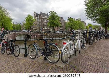 AMSTERDAM, NETHERLANDS - MAY 12, 2016: Bicycles lining a bridge over the canals of Amsterdam, Netherlands. Cycling is one of the best ways to get around the city. - stock photo