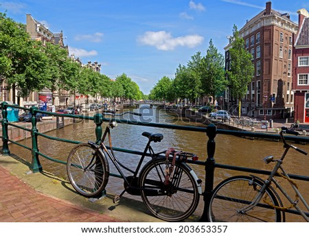AMSTERDAM, NETHERLANDS - MAY 30: Bicycles on a bridge over the canal on May 30, 2014 in Amsterdam, Netherlands. Bikes are very popular in the Netherlands, the average Dane travels 900 km per year.