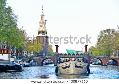 Amsterdam, Netherlands - May 04, 2016 - Excursion sightseeing boat with Montelbaanstoren tower on bank of the canal Oudeschans, built in 1516 for the purpose of defending the city - stock photo