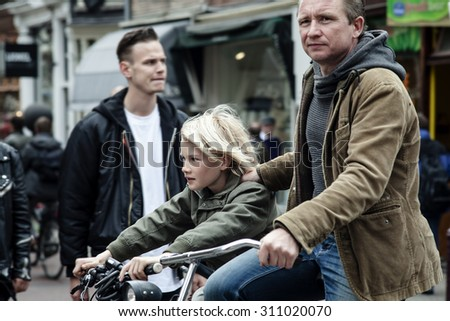 AMSTERDAM, NETHERLANDS - MAY 9:  Father with son riding bicycles in historical part in Amsterdam, Netherlands on May 9, 2015 - stock photo