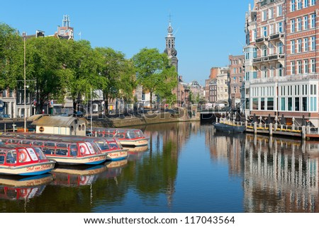 AMSTERDAM, NETHERLANDS - MAY 28: Sightseeing boats on a canal on May 28, 2012 in Amsterdam. Having a population of more than 750,000  Amsterdam is visited with over 3,5 million foreign visitors a year