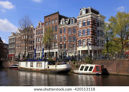 AMSTERDAM, NETHERLANDS - MAY 4, 2016: View of traditional houses and boats in Jordaan neighborhood and canals of Amsterdam, Netherlands. Amsterdam is capital and most populous city of Netherlands   - stock photo
