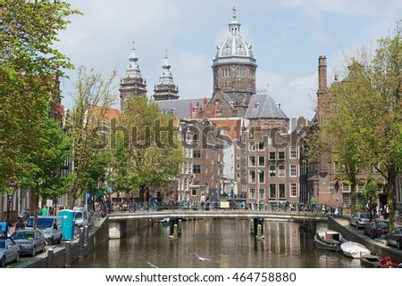 AMSTERDAM, NETHERLANDS - MAY 30, 2013: View to the canal and basilica of Saint Nicholas in Amsterdam, Netherlands.