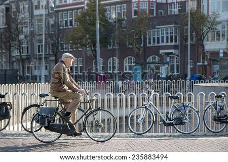 AMSTERDAM, NETHERLANDS - NOV 2014 - An old man making his morning bicycle commute over a canal bridge in the Autumnal Sunshine near Keizersgracht. - stock photo