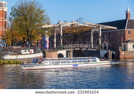 AMSTERDAM, NETHERLANDS - NOVEMBER 13: canal with drawbridge excursion boat and unidentified people on November 13, 2014 in Amsterdam, a city with historical canals n more than 3.66 mio visitors a year - stock photo