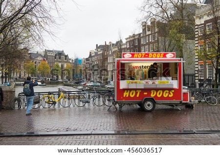 AMSTERDAM, NETHERLANDS - NOVEMBER 15, 2015: Vendor with a hot-dogs stall on a rainy day in the center of amsterdam