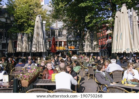 AMSTERDAM, NETHERLANDS-OCT 11: People enjoying a sunny day on the Leidseplein in Amsterdam on Oct 11, 2008. The Leidseplein is famous for its terrace especially with tourists - stock photo