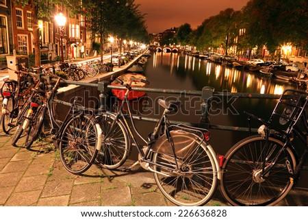 AMSTERDAM, NETHERLANDS, October, 5 :Amsterdam canal bridge bicycles night illumination. Holland, Netherlands,October 11, 2014   - stock photo
