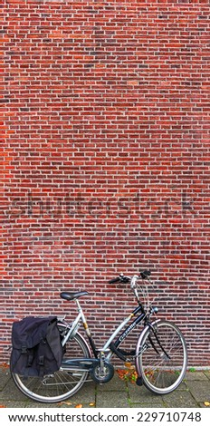 AMSTERDAM, NETHERLANDS,OCTOBER,10: Bicycle on parking near a red brick wall. Vertical panorama.  Amsterdam - the bicycle capital of Europe, on October 10, 2014, Netherlands  - stock photo