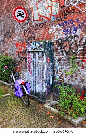 AMSTERDAM,NETHERLANDS,OCTOBER,07:Bicycle street parking near the red brick wall with graffiti.Amsterdam - the bicycle capital and one of the most  original special cities of Europe on October 07,2014  - stock photo