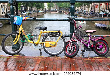 AMSTERDAM, NETHERLANDS,OCTOBER,09: Color children's bicycles parked on the bridge of the Amsterdamcanal in rainy autumn day. Amsterdam - the bicycle capital of Europe, October, 09, 2014, Netherlands - stock photo