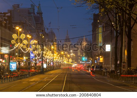 AMSTERDAM, NETHERLANDS - OCTOBER 23: Night view, with light trails of trams and cars, of the Central Station in Amsterdam , on October 23, 2012 in Amsterdam, Holland. - stock photo