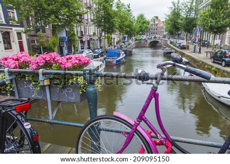 Amsterdam, Netherlands, on July 8, 2014. Bicycles are parked on the city street on the bank of the channel - stock photo