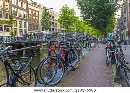 Amsterdam, Netherlands, on July 10, 2014. Bicycles are parked on the city street on the bank of the channel