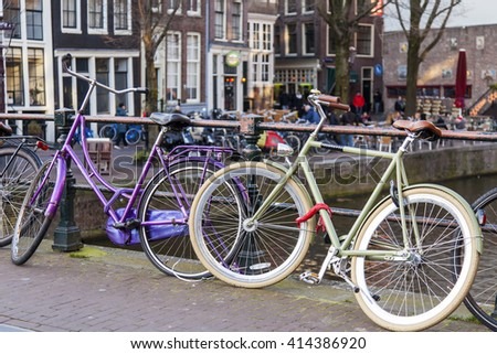 AMSTERDAM, NETHERLANDS on MARCH 27, 2016. City landscape. Bicycles are parked on the bridge via the channel