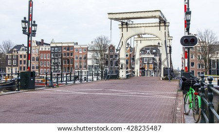 AMSTERDAM, NETHERLANDS on MARCH 31, 2016. Typical urban view in the spring. An old movable bridge through the canal and buildings of the XVII-XVIII construction on embankments