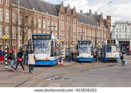 AMSTERDAM, NETHERLANDS on MARCH 27, 2016. Typical urban view in the spring evening. The tram moves down the street