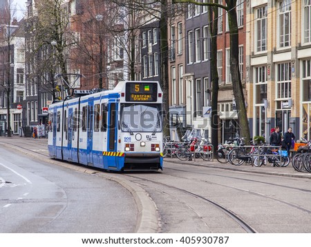 AMSTERDAM, NETHERLANDS on MARCH 27, 2016. Typical urban view in the spring morning. The tram moves down the street