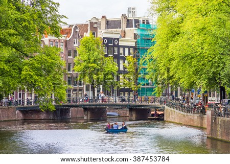 AMSTERDAM, NETHERLANDS - SEPTEMBER 3, 2012: Tourists sailing on a canal in Amsterdam. Amsterdam is the capital of the Netherlands and the canals and harbours fill a full quarter of the city surface. - stock photo