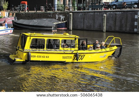AMSTERDAM, NETHERLANDS - SEPTEMBER 22, 2011: Water taxi transporting unidentified people along Amsterdam's waterways (canals). Typical mean of transport in Amsterdam.