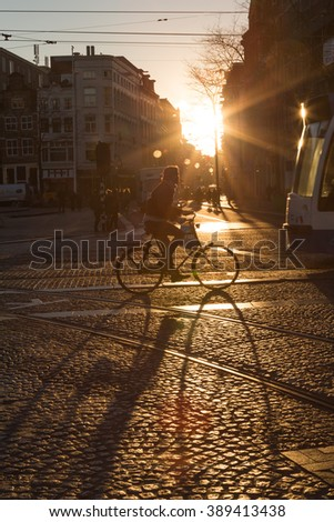 AMSTERDAM, NETHERLANDS - 16TH FEBRUARY 2016: A cyclist on a road in Amsterdam at sunrise. The sun can be seen behind the bike and shadows can be seen in the foreground. - stock photo