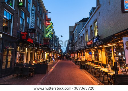 AMSTERDAM, NETHERLANDS - 16TH FEBRUARY 2016: A view down Korte Leidsedwarsstraat in Amsterdam at night. A Coffee Shop, restaurants and people can be seen. - stock photo