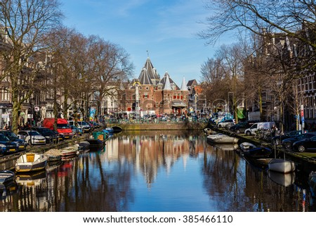 """AMSTERDAM, NETHERLANDS - 16TH FEBRUARY 2016: A view towards The Waag (""""weigh house"""")  in Amsterdam from the Kloveniersburgwal canal. People, cars, bikes and other buildings can be seen. - stock photo"""