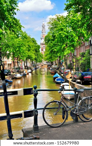 amsterdam, netherlands: typical canal scene with southern church and bicycle.