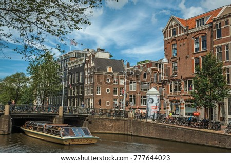 Amsterdam, northern Netherlands - June 26, 2017. Tree-lined canal with old brick buildings, bridge, boat and blue sky in Amsterdam. Famous for its huge cultural activity, graceful canals and bridges.