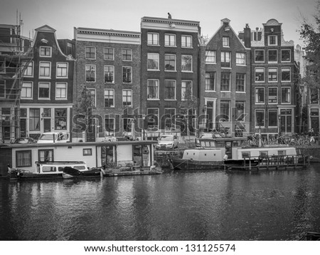 AMSTERDAM - NOV 21: Dutch scenery with its canals, houseboats and canal front houses. Row of historical crooked merchant houses facing a canal in Amsterdam on Nov 21, 2012 - stock photo