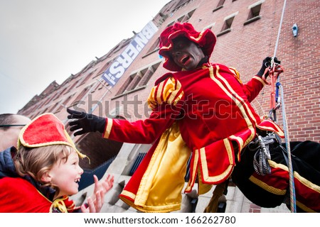 AMSTERDAM - NOVEMBER 17: A man wears a costume of Zwart Piet during Sinterklaas arrival on November 17, 2013 in Amsterdam. Zwarte Piet's guise is criticized for encouraging racial stereotypes. - stock photo