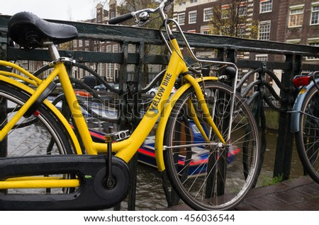 AMSTERDAM - NOVEMBER 15, 2015: Yellow rental bike on a bridge. The number of bicycles equal the number of residents in the dutch capital - stock photo
