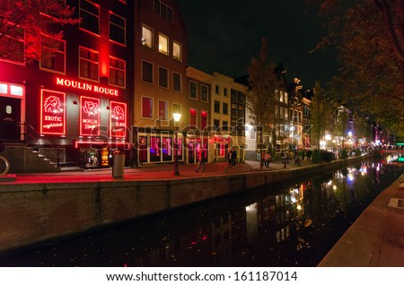 AMSTERDAM - OCTOBER 22, 2013: Red-light district in Amsterdam on October 22, 2013 in Amsterdam, Netherlands. There are about three hundred cabins rented by prostitutes in the area. - stock photo