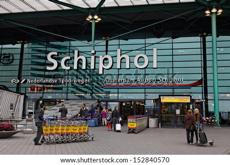 AMSTERDAM- OCTOBER 31:Unidentified people doing various activities in front of the main entrance in Schiphol Airport, the Netherlands' main international airport on October 31 2011 in Amsterdam. - stock photo