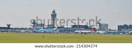 AMSTERDAM/SCHIPHOL, THE NETHERLANDS, 27 August 2014 - Panoramic view of Amsterdam Airport Schiphol with control tower and airplanes. - stock photo