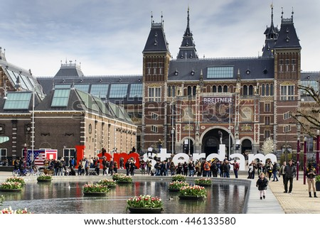 AMSTERDAM, THE NETHERLANDS - APRIL 9, 2016: Bunch of tulips in the pool in front of the Rijksmuseum (National state museum), a popular touristic destination in Amsterdam.