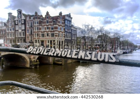 AMSTERDAM, THE NETHERLANDS: APRIL 7, 2016 - View of the old bridge railing with their name and the background of the city and canal. - stock photo