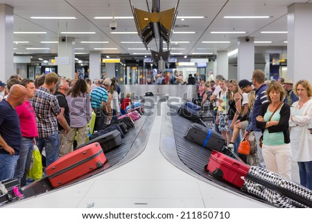 AMSTERDAM, THE NETHERLANDS - AUG 14: Airplane travelers are waiting for their luggage from a conveyor belt at Schiphol airport on August 14, 2014 in Amsterdam, The Netherlands - stock photo