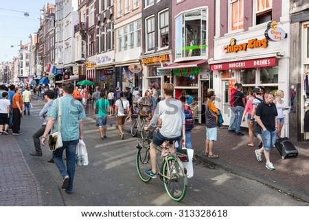 AMSTERDAM, THE NETHERLANDS - AUG 06: Tourists in Amsterdam shopping and looking for a restaurant on August 06, 2015 downtown in Amsterdam, the Netherlands - stock photo