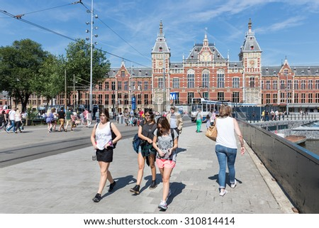 AMSTERDAM, THE NETHERLANDS - AUG 06: Tourists walking in front of the central station on August 06, 2015 in Amsterdam, capital city of the Netherlands - stock photo