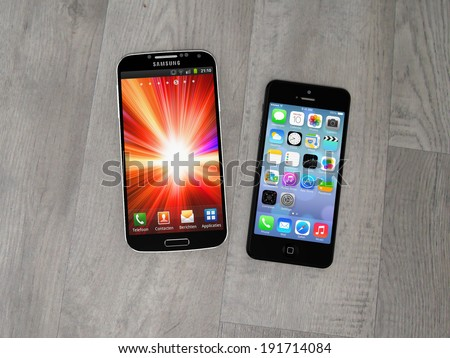 AMSTERDAM, THE NETHERLANDS - CIRCA APRIL 2014 - Samsung Galaxy S smartphone and Apple iPhone. - stock photo
