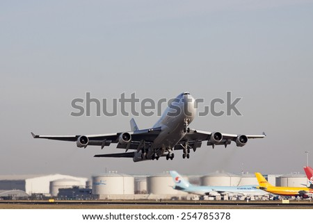 AMSTERDAM, THE NETHERLANDS - FEBRUARY 18, 2015:  Boeing 747 cargo plane just taken off from the runway in front illuminated by the sun on february 18 , 2015 in Amsterdam, Holland. - stock photo